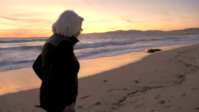 An attractive active mature woman talking and walking on beach at sunset video