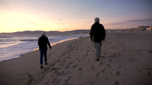 An attractive older couple walking on the beach at dusk video