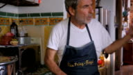 An elder man with an apron walks towards a middle aged man in kitchen video