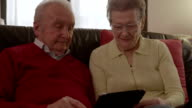 An elder senior couple sitting on the couch with a tablet while they are browsing the internet, watching videos and commenting the contents video