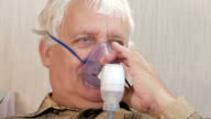 An elderly man holding a mask from an inhaler at home. Treats inflammation of the airways via nebulizer. Preventing asthma and cough. Close-up video