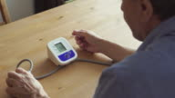 BACK VIEW: An elderly man measuring the blood pressure at home video