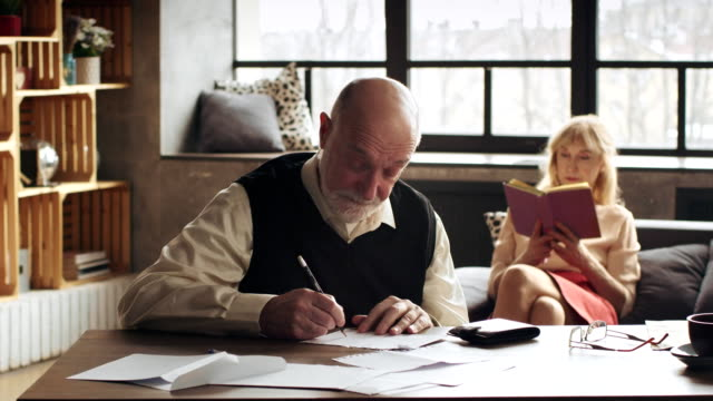 an elderly man writes a letter to her longtime friend and looking for coins on a stamp for the envelope video