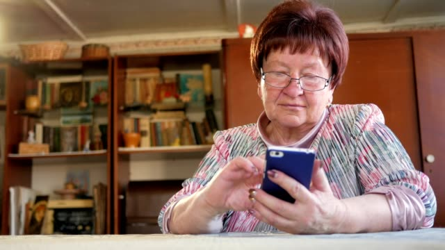 An elderly woman writes a text message on her mobile phone. She carefully presses on the screen and pronounces the text video
