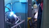 An employee in a special protective suit oversees the process works welding apparatus. Control the man behind the automatic machine for the production of metal parts video
