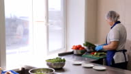 An employee of catering company arranges chopped vegetables video