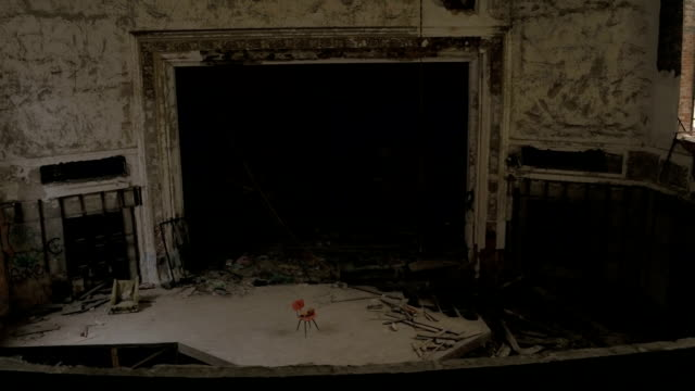 An empty chair on eerie stage in abandoned old theatre in crumbling cathedral video