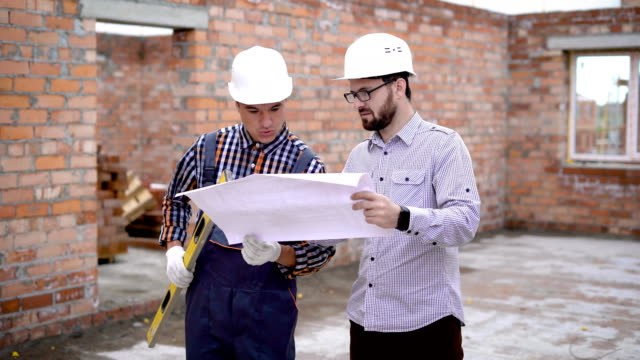 An engineer in a helmet and an adult bearded architect consider a construction drawing where the scheme for the reconstruction of a country house is indicated video