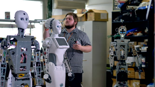 An engineer installs a back head cover on a robot. video