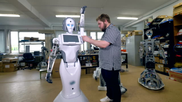 An engineer screws on an outer shell on a robot. video