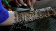An Indian lady applying a henna tattoo video