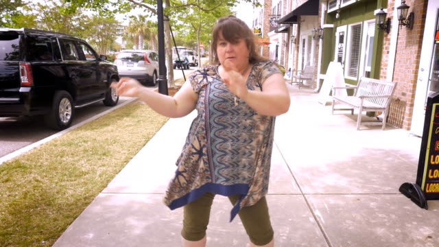 An obese woman pointing and dancing around celebrating success video