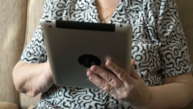 An old woman viewing photos using a digital tablet video