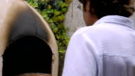 An older father and son look at the progress inside a wood fired oven video