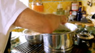 An older Jewish man stirs a large pot of soup with herbs in it in slow motion video