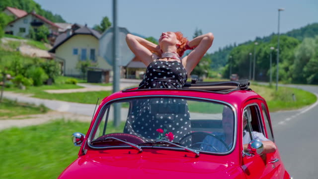 An older lady stands up and puts her hands up during a car ride in a red yugo video
