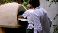 An older man flips homemade matzah in a wood burning oven in slow motion video