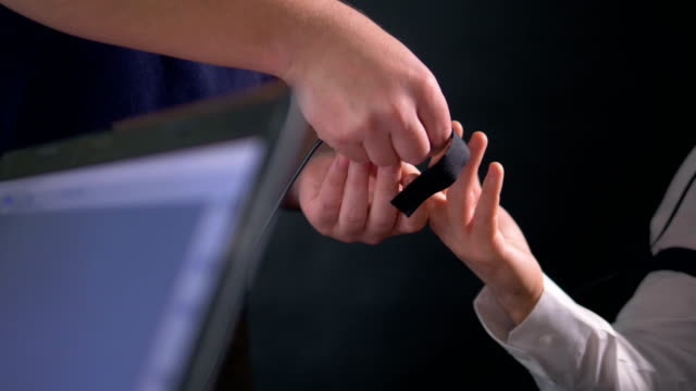 An operator attaches an electrode on a subject s finger. video
