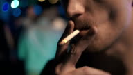 an smoking a cigarette at night club, close up, slow motion, low light video