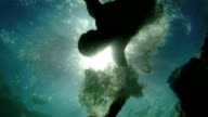 An underwater shot of a jumping man against bright sunshine.Slow motion video. video
