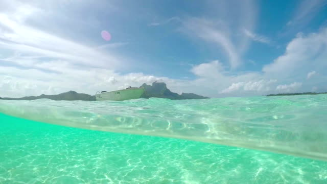 HALF UNDERWATER: Anchored boat in front of exotic Bora Bora video