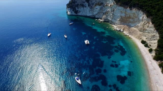 Anchored sailboats in calm water bay video
