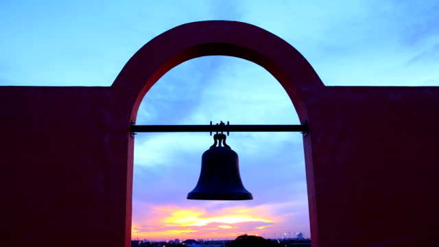 Ancient Bell against colorful sunset video