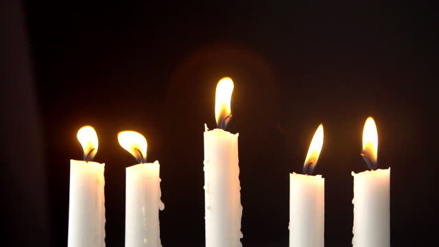 Сandles burning in the dark, yellow flame of a candle. Slow motion video