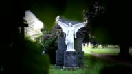 Angel Statue on cemetery covered with leaves video