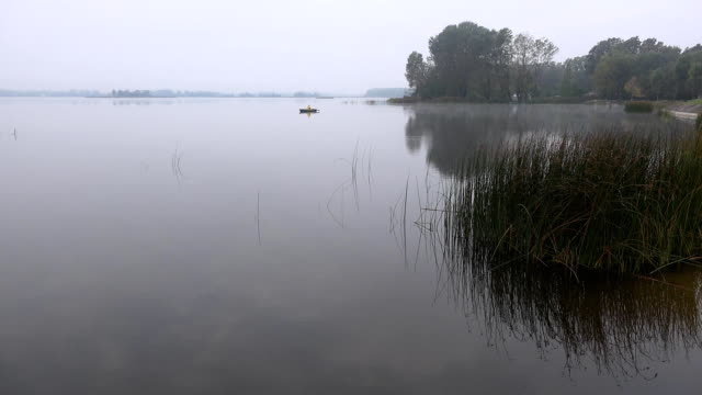 Angler man row sitting in wooden boat rowboat on lake cover with dense fog. FullHD video