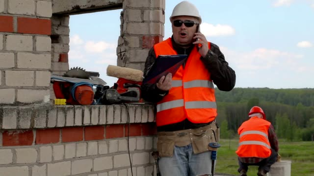 Angry builder talking on smart phone video