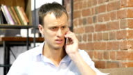 Angry businessman talking on the phone.Upset depressed businessman video