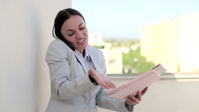 Angry businesswoman with cellphone and documents, outdoors video