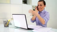Angry businesswoman with cellphone and laptop in the office video
