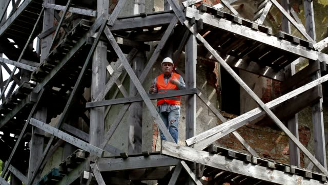 Angry construction worker standing on wooden scaffolding and talking video