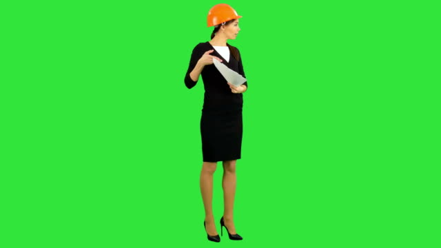 Angry female chief engineer with documents arguing with workers on a Green Screen, Chroma Key video