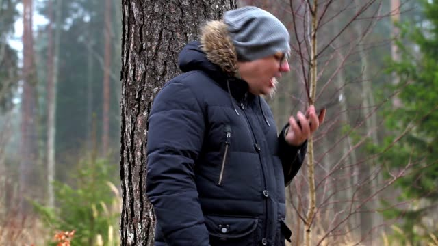 Angry man with smart phone in forest video