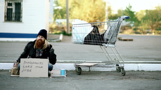 Angry upset young homeless man with cardboard sitting near shopping cart and drink alcohol at cold day because of immigrants crisis in Europe video