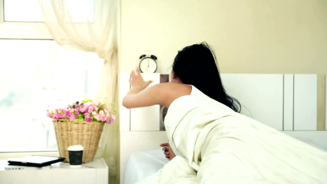 Angry woman lying a bed and holding an alarm clock video