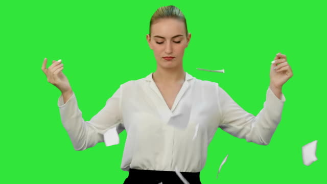 Angry young woman rips paper documents, throw it at the camera on a Green Screen, Chroma Key video