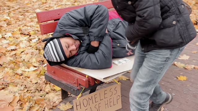 Anonymous benefactor giving generous charity donation to sleeping homeless man video