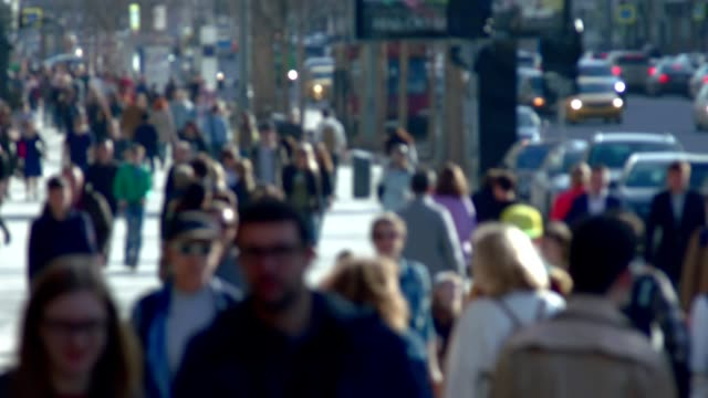 Anonymous crowd of people walking on street slow motion video