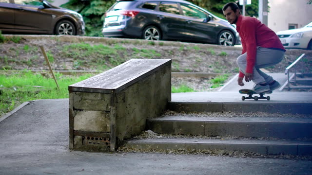Anonymous man doing skateboarding trick on street in summer video