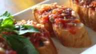 Antipasto Bruschetta, baguette slices topped with tomatoes basil mixed sauce video