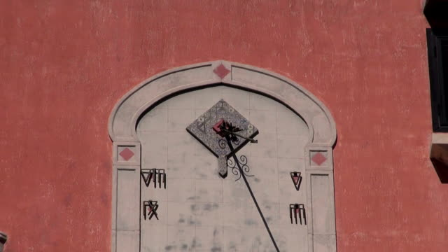 Antique sundial on stone wall of antique building sunny day video