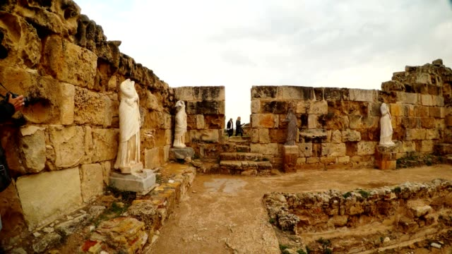 Antique white headless statues room with pool tourists in the doorway ancient town Salamis video