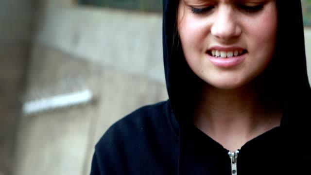 Anxious teenage girl standing in black hooded jacket video