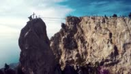 Apic aerial shot of man walking suspension bridge to Cross in Crimea. High rocks Ai-Petri of Crimean mountains. Black sea coast city and blue sky with clouds. video