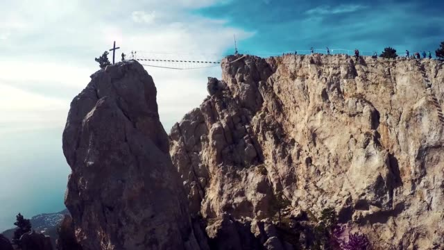 Apic aerial shot of man walking suspension bridge to Cross in Crimea. High rocks Ai-Petri of Crimean mountains. Black sea coast city and blue sky with clouds. video