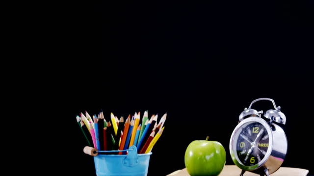 Apple and alarm clock on book stack with school supplies video